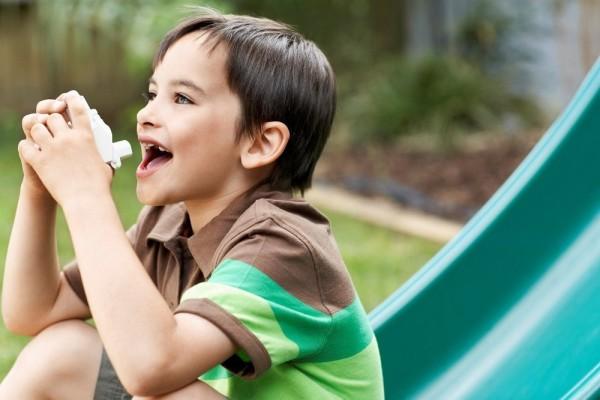 astmatický chlapec s inhalátorem