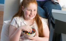 Obézní dívka sleduje TV