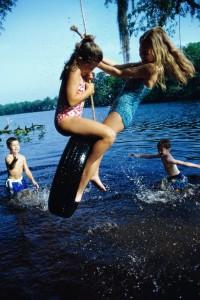 na houpačce nad vodou dovádí děti