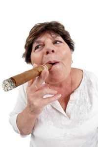 Photo of a woman in her sixties happily smoking a large cuban cigar. Taken with a fisheye lens.